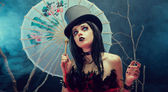 Attractive gothic girl in top hat with Chinese umbrella looking — Stock Photo