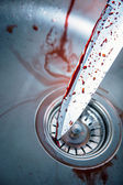 Bloody knife in kitchen sink — Stock Photo