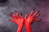 Red devil hands with sharp black nails, extreme body-art — Stock Photo