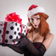Pretty redhead pin-up girl in Santa Claus hat holding gift box — Stock Photo