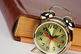 Golden alarm clock on the book — Stock Photo