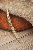 Rye bread, and corn on a wooden table — Stock Photo