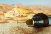 Bottle under an umbrella on the sand — Stock Photo