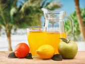 Verscheidenheid van fruit en sap op een strand-tabel — Stockfoto