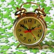 Alarm clock on the green puzzle - Stock Photo