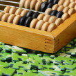 Wooden abacus on pile of green puzzle - Stock Photo