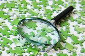 Magnifying glass on the green puzzle — Stock Photo