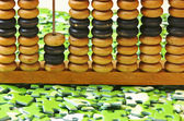 Wooden abacus on pile of green puzzle — Stock Photo