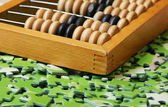 Wooden abacus on pile of green puzzle — Stockfoto