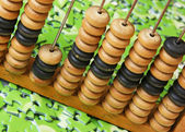 Wooden abacus on pile of green puzzle — Stock fotografie