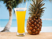Glass of juice and pineapple on the beach — Stock Photo