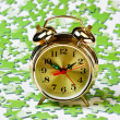 Alarm clock on the green puzzle — Stock Photo