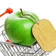 Green apple with tag in shopping carts isolated on white backgro - Stock Photo