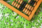 Wooden abacus on pile of green puzzle — Foto de Stock