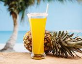 Pineapple juice and pineapple on the beach — Stock Photo