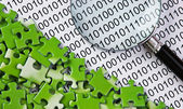 Puzzles and magnifying glass on a binary code — Foto Stock