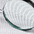 Magnifying glass on a binary code — Stock Photo #13354869