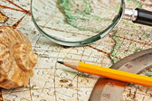 Magnifying glass and a pencil on a map — Stock Photo