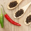Black and red pepper in wooden spoon on the old board — Stock Photo