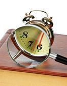 Despertador dorado y la lupa en el libro aislado — Foto de Stock