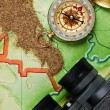 Binoculars and a compass on the map with sand — Stock Photo