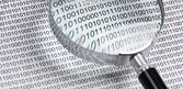 Magnifying glass on a binary code — Stock Photo