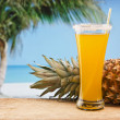 Pineapple juice and pineapple on the beach — Stock Photo