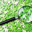 Magnifying glass on pile of green puzzle — Stock Photo #13718513