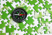 Compass on the green puzzle — Stock Photo