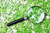 Magnifying glass on pile of green puzzle — Foto de Stock