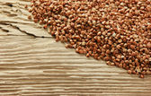 Buckwheat groats on a wooden table — Stock Photo