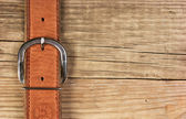 Vintage belt buckle on a old wooden board — Stock Photo