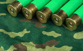 Old hunting cartridges on camouflage background — Stock Photo