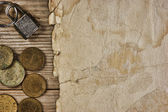 Old paper and coins on a wooden table — Stock Photo