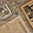 Old notes and coins and abacus on a wooden table — Stock Photo #13731321