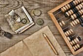 Old notes and coins and abacus on a wooden table — Stock Photo
