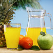 Variety of fruit and juice  on a beach table — Stock Photo