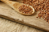 Buckwheat groats and wooden spoon — Stock Photo
