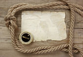 Vintage paper with compass and rope on old wooden boards — Stock Photo