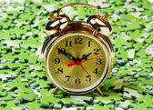 Alarm clock on pile of green puzzle — Stock Photo