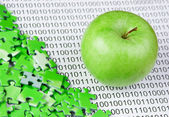 Green apple and puzzles on a binary code — Stock Photo