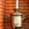 Old brass samovar on a brick kitchen - Stock Photo