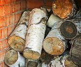 Birch wood in the brick fireplace — Stock Photo