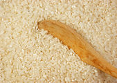 Raw rice and wooden spoon — Stock Photo