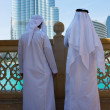 Two anonymous Arab men in traditional white clothing  looking at - Stock Photo