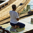 An unidentified man - boatman sitting in a boat and prays - Stock Photo