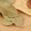 Dry bay leaf on a wooden kitchen cutting board - Stock Photo