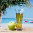 Glass of apple juice on a beach table - Foto Stock