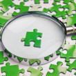 Magnifying glass on the green puzzle — Stock Photo #16247953