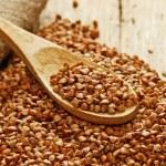 Buckwheat groats and wooden spoon — Stock Photo #16247979